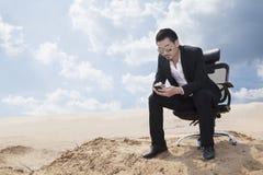Jeune homme d'affaires dans des lunettes de soleil se reposant dans une chaise de bureau au milieu du désert, vérifiant son téléph Images libres de droits