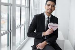 Jeune homme d'affaires dans l'amour se reposant sur le rebord de fenêtre Photo stock