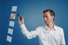 Jeune homme d'affaires dans la chemise blanche vérifiant la boîte de liste de contrôle Fond pour une carte d'invitation ou une fé Photographie stock