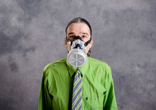 Jeune homme d'affaires dans la chemise verte avec le masque de gaz photographie stock