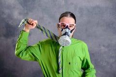 Jeune homme d'affaires dans la chemise verte avec le masque de gaz photo libre de droits