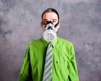 Jeune homme d'affaires dans la chemise verte avec le masque de gaz image libre de droits