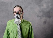 Jeune homme d'affaires dans la chemise verte avec le masque de gaz image stock