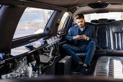 Jeune homme d'affaires dans la limousine dactylographiant au téléphone intelligent Image stock