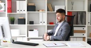 Jeune homme d'affaires dans la veste grise se reposant à la table dans le bureau blanc, regardant l'horloge et partant sur la cha banque de vidéos