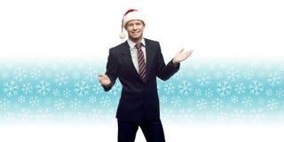 Jeune homme d'affaires dans le chapeau de Santa montrant l'espace vide au-dessus de l'hiver Images stock