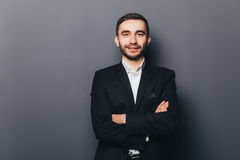 Jeune homme d'affaires dans le costume avec les mains croisées Images stock