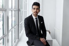 Jeune homme d'affaires dans le costume noir se reposant sur le rebord de fenêtre Photographie stock
