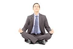 Jeune homme d'affaires dans le costume se reposant sur un plancher et méditant Photo stock