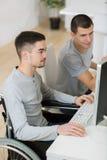 Jeune homme d'affaires dans le fauteuil roulant et l'ami avec l'ordinateur Photo libre de droits