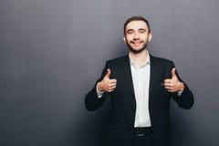 Jeune homme d'affaires dans le geste superbe de costume Image stock