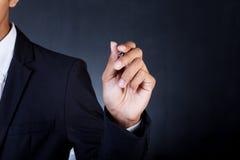 Jeune homme d'affaires dans le stylo de participation de costume Image stock