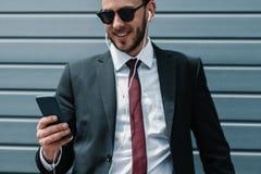 Jeune homme d'affaires dans les lunettes de soleil et des écouteurs utilisant le smartphone Image stock