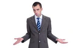 Jeune homme d'affaires dans un costume gris rejetant la responsabilité, photo stock