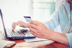 Jeune homme d'affaires de F travaillant sur son ordinateur portable et employant la carte de crédit se reposant à la table en boi Images libres de droits