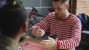 Jeune homme d'affaires de hippie expliquant des détails de projet à l'équipe ethnique multi montrant le plan de papier dans la fi banque de vidéos