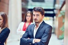 Jeune homme d'affaires de Smilling dans l'avant que son équipe blured à l'arrière-plan Photographie stock libre de droits