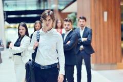 Jeune homme d'affaires de Smilling dans l'avant que son équipe blured à l'arrière-plan Photographie stock