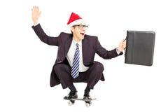 Jeune homme d'affaires de sourire avec la serviette et le chapeau de Santa sur un s Photographie stock