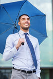 Jeune homme d'affaires de sourire avec le parapluie dehors Photographie stock libre de droits