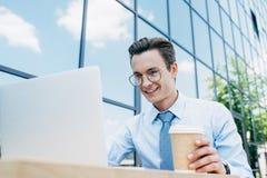 jeune homme d'affaires de sourire bel dans des lunettes utilisant l'ordinateur portable et tenir la tasse de papier en dehors de  images libres de droits