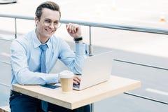 jeune homme d'affaires de sourire dans des lunettes utilisant l'ordinateur portable photographie stock