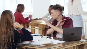 Jeune homme d'affaires de sourire heureux causant en passant au collègue féminin s'asseyant à la table de bureau dans coworking à clips vidéos