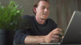 Jeune homme d'affaires de sourire joyeux s'asseyant à l'ordinateur et dactylographiant aux messages d'ordinateur portable Homme d banque de vidéos