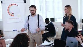 Jeune homme d'affaires de sourire professionnel heureux menant la discussion animée d'échange d'idées avec l'équipe diverse lors  banque de vidéos