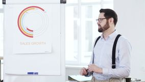 Jeune homme d'affaires de sourire réussi heureux présent le diagramme de ventes sur le flipchart aux travailleurs lors de la réun banque de vidéos