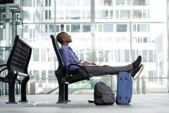 Jeune homme d'affaires de sourire s'asseyant avec l'ordinateur portable et le bagage Photos libres de droits