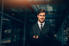 Jeune homme d'affaires de sourire se tenant avec ses bras croisés Photos stock