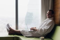 Jeune homme d'affaires de sourire travaillant au peignoir blanc de port d'ordinateur portable se reposant près de la fenêtre avec Images libres de droits