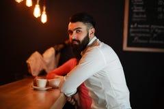 Jeune homme d'affaires derrière la barre avec du café Image stock