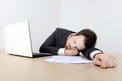 Jeune homme d'affaires dormant sur le bureau Image stock