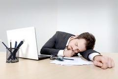 Jeune homme d'affaires dormant sur le bureau Image libre de droits