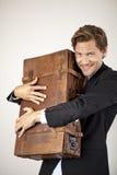 Jeune homme d'affaires embrassant sa vieille valise Photographie stock libre de droits