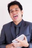 Jeune homme d'affaires ennuyé tenant un comprimé photographie stock