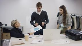 Jeune homme d'affaires et deux femmes d'affaires discutant leur projet d'habillement et examinant des documents clips vidéos
