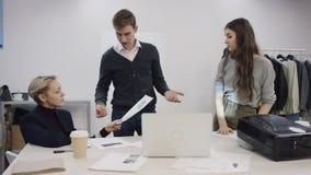 Jeune homme d'affaires et ses associés féminins discutant leur plan d'action clips vidéos