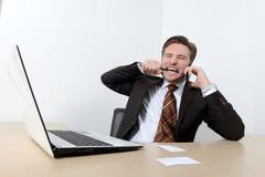 Jeune homme d'affaires fâché cassant un crayon avec des dents Photos stock