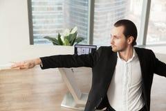 Jeune homme d'affaires faisant le yoga sur le lieu de travail dans la pose de guerrier image stock