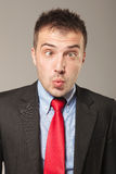 Jeune homme d'affaires faisant un visage drôle photos stock