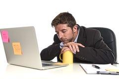 Jeune homme d'affaires fatigué et gaspillé travaillant dans l'effort à l'ordinateur portable de bureau semblant épuisé Image stock