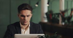 Jeune homme d'affaires fatigué s'asseyant à une table dans un fonctionnement de café sur un ordinateur portable Indépendant, comm clips vidéos