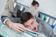 Jeune homme d'affaires fatigué s'asseyant sur le lieu de travail photographie stock libre de droits