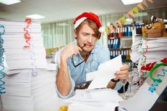 Jeune homme d'affaires fatigué s'asseyant sur le lieu de travail parmi des papiers le jour de Noël Images stock