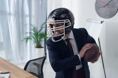 jeune homme d'affaires furieux dans le casque jouant le rugby Image libre de droits