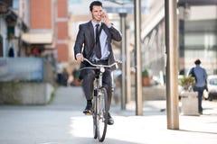 Jeune homme d'affaires gai montant une bicyclette et à l'aide du téléphone photo stock