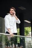 Jeune homme d'affaires gai se tenant et parlant au téléphone portable photographie stock libre de droits